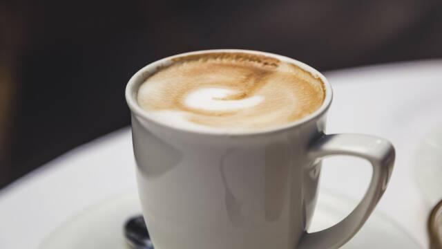 En café latte serveret i en hvid kop.