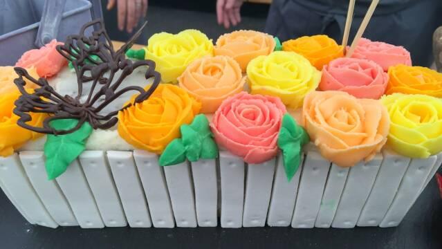 Billede af kage udformet som et blomsterbed med sommerfugle