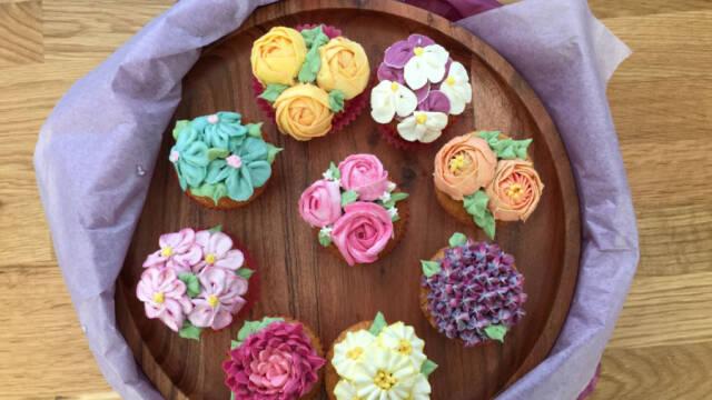 farverige cupcakes med smørblomster på træfad
