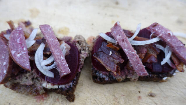 Lun leverpostej med rugbrød og bacon på skærebræt