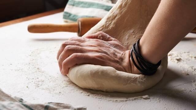 En pizzadej æltes i hånden.