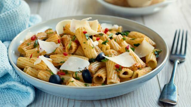 En tallerken med pastasalat med rød pesto og parmesan ovenpå.