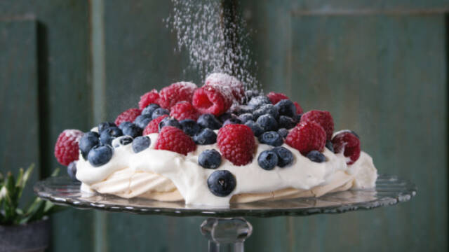 Pavlova på højt fad med bær og drys af flormelis