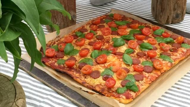 En smuk pizza med tomater, basilikum og pesto