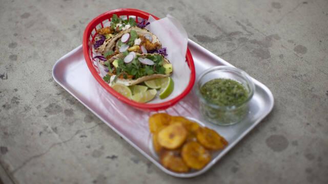 En popcorn chicken taco på et metalfad i en rød plastikskål. Ved siden af er en hjemmelavet salsa.