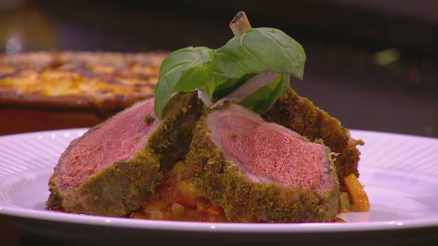 Billedet viser en portionanrettet lammekød på en ratatoille. I baggrunden ses en kartoffelgratin.