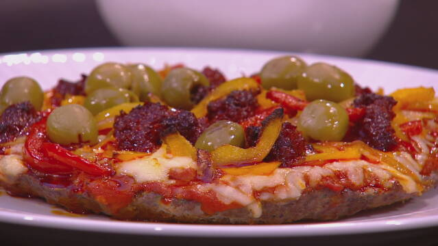 Billedet viser et stykke meatza toppet med oliven.