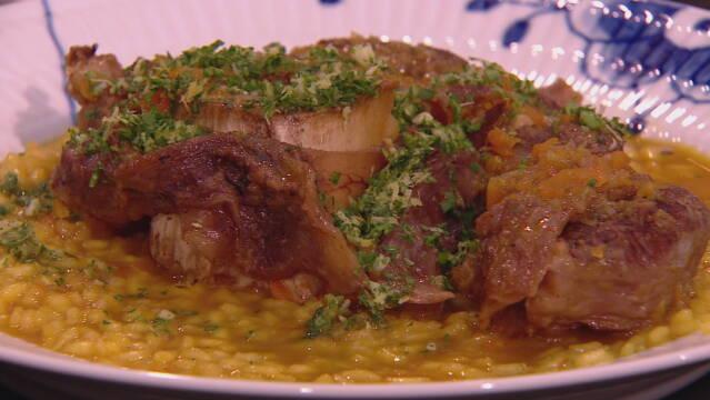 Billedet viser den italienske ret osso buco serveret på risotto.