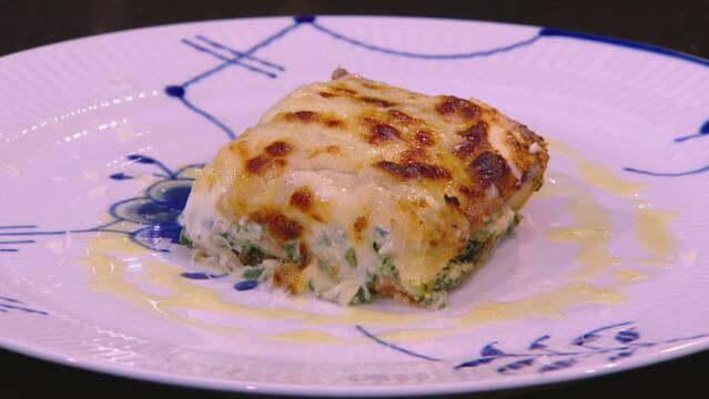 Billedet viser et stykke gnocchi lasagne med spinat.