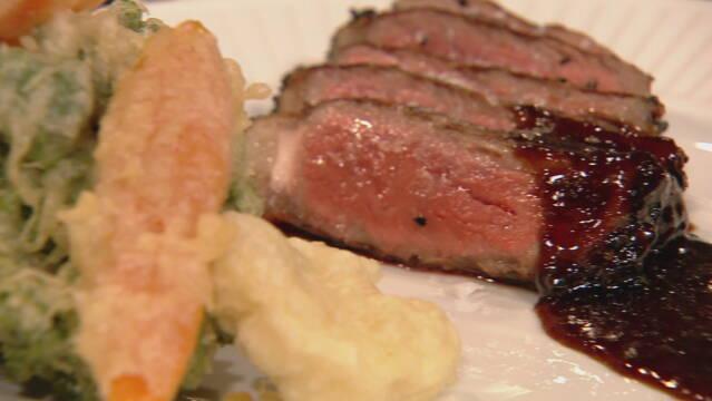 Billedet viser skiver af japansk/fransk steak med sauce og tempurastegte grøntsager.