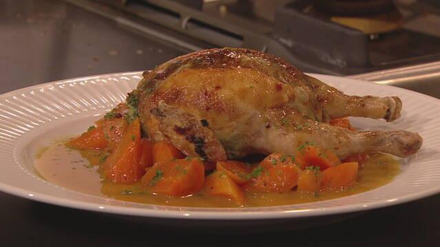 Billede af udbenet farseret poussin anrettet på glaserede gulerødder og en lækker sauce.