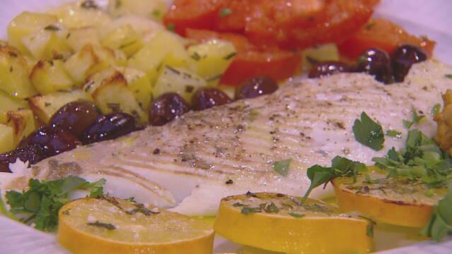 Billedet viser ovnstegt pighvar, oliven, kartofler og tomater.