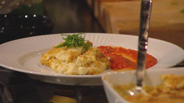 Billede af brandafe a la morue (klipfiske-gratin) med tomatsauce, pyntet med lidt basilikum.