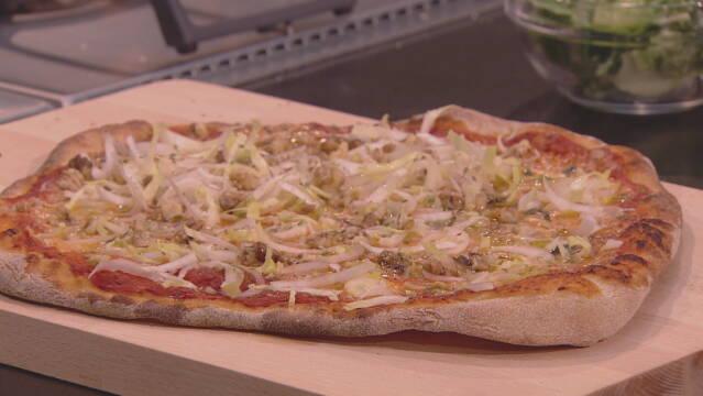Billedet viser en hjemmelavet pizza med gorgonzola, endivesalat og valnødder.