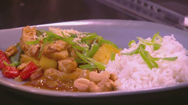 Billedet viser en portion ris anrettet med kylling, grøntsager og cashewnødder.