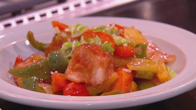 Billedet viser en portion ris med friturestegt kylling og sursød sauce.