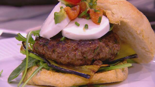 Billedet viser en dejlig burger med æg og aubergine, drysset med lidt purløg.