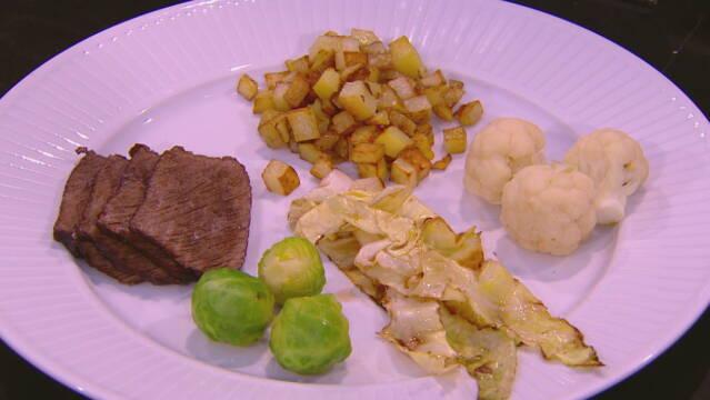 Billedet viser en oksetykkam serveret med blomkål, rødkål, spidskål og kartofler.