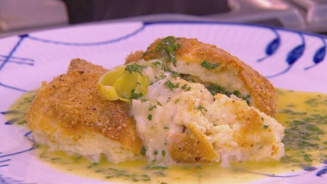 Billedet viser fiskegratin med sauce beurre blanc, drysset med lidt persille og serveret med en skive citron.