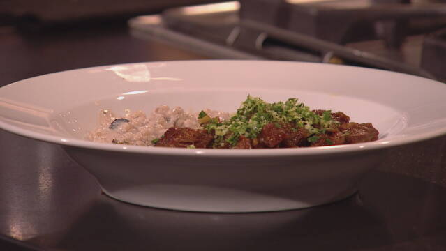 Billede af lammeragout serveres med en bygotto og pyntet med en gremolata.
