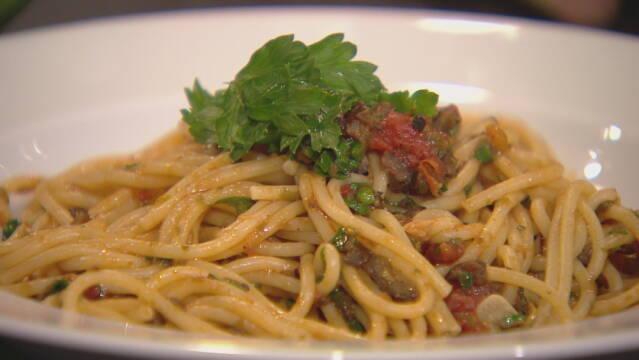 Billede af spaghetti puttanesca pyntet med bredbladet persille.