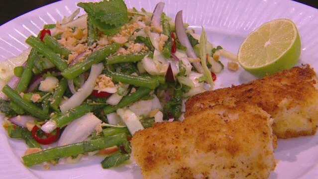 Billedet viser 2 stykker paneret fisk, en asiatisk salat og en halv lime.