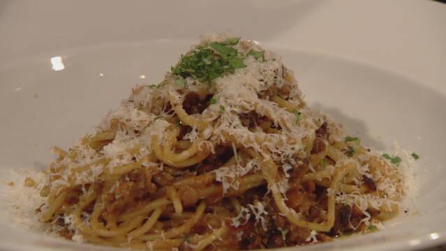 Spaghetti bolognese drysset med frisk basilikum og friskrevet parmesanost.