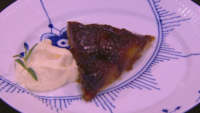 Billede af tarte tatin med mascarponecreme pyntet med en kvist rosmarin.