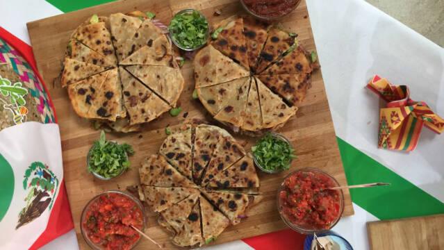 Quesadillas skåret i stykker på et skærebræt med små skåle med salsa og koriander