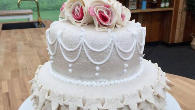 hvid bryllupskage pyntet med marcipanovertræk og roser på toppen