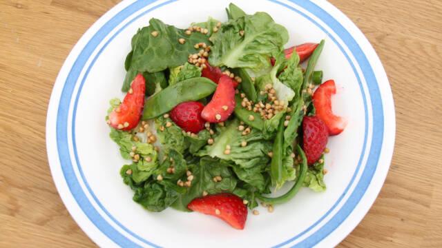En tallerken med salat, jordbær og ærter.