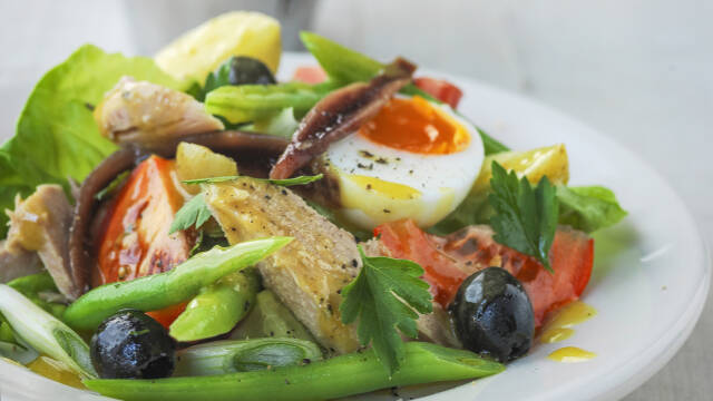 En salade nicoise med æg, tomater, oliven, tun og ansjoser.