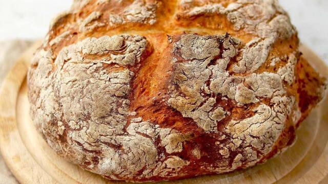 Et stort, velbagt brød på et træskærebræt