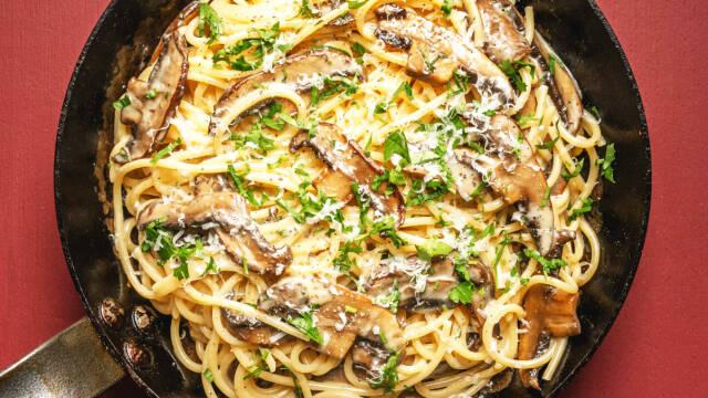 En pande med spaghetti carbonara med svampe og persille.