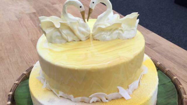 bryllupskage med gul glaze pyntet med to bolchesvaner