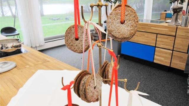 Flere svenske møllehjul af knækbrød med kanel hænger i snore fra stativ