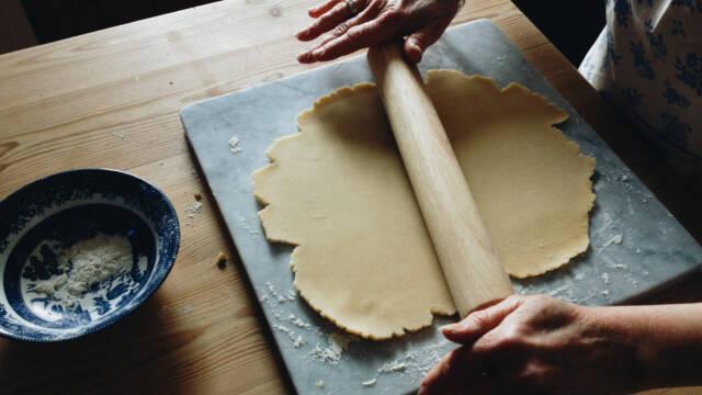 Hænder ruller tærtedej ud