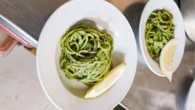 pasta med pesto og citronbåd på hvid tallerken