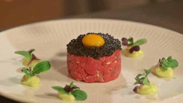 Smuk ret af frisk tatar toppet med æggeblommer, ægte kaviar og friske urter.