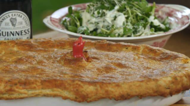 En tærte med en øl og salat i baggrunden