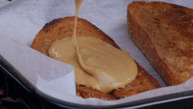 Ristet brød i et fad med ostesovs hældt over.