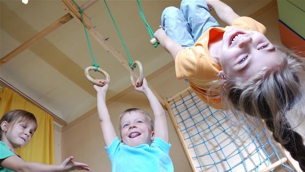 dei bambini che giocano uno sul trapezio uno sugli anelli una bambina ride